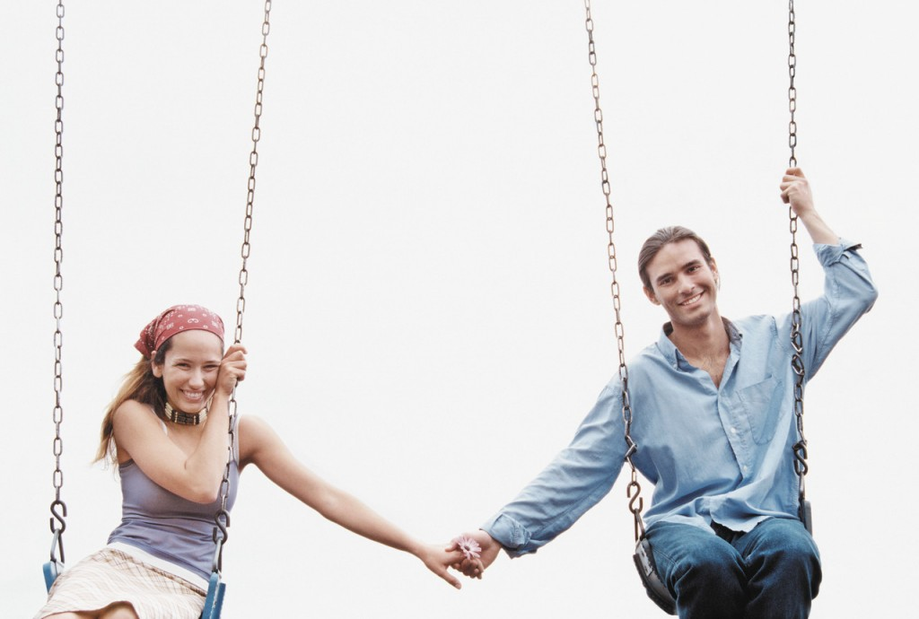 Couple Holding Hands on Swing Set