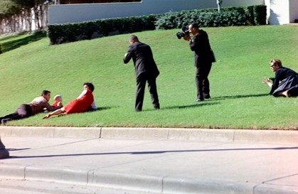 Frightened onlookers lay on the grass in reaction to shots fired as cameramen record their actions at Dealey Plaza in Dallas, TX, 22 November 1963.  Photo credit: Cecil Stoughton. White House Photographs. John F. Kennedy Presidential Library and Museum, Boston