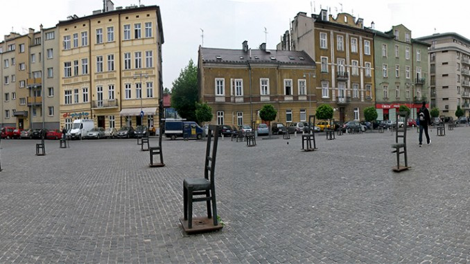 """Formerly known as Concordia Square, this served as the central square of the Kraków ghetto and the deportation spot of Kraków Jews between 1941-43. The square was refurbished at the end of 2005 and the memorial installed. It features 33 large illuminated chairs in the square and 37 smaller chairs standing on the edge of the square and at the tram stops. The chairs represent the furniture and other remnants that were discarded on that very spot by the ghetto's Jews as they were herded into the trains that would often take them to concentration camps. One of the memorial's designers, Piotr Lewicki, said: """"First, a quarter of the town's residents had to leave their homes and go to the closed-off area of Podgórze. Then the ghetto was reduced in size, and the people were divided according to whether or not they could work, whether they were sick or healthy etc. As a result people were constantly resettling, bringing all their belongings with them. They also took chairs with them, the furniture closest to the body. When the ghetto was liquidated, the Jews had to move to the Płaszów camp, and anything that wasn't needed remained in the square. We wanted to draw reference to that moment precisely. There must have been an incredible silence, it must have been completely empty."""" (Photo by Jennifer Boyer via Flickr.com. Used under Creative Commons 2.0 License)"""